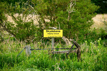 no entrance: Yellow sign in danish saying - Shooting range, No entrance, when the flag or ball is raised - standing at the militaries exercise area in Sandholm, Denmark Stock Photo