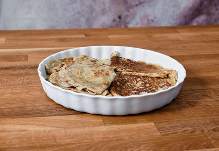 plate of white china, with a bunch of folded pancakes, standing on a table of dark brown laminated hardwood