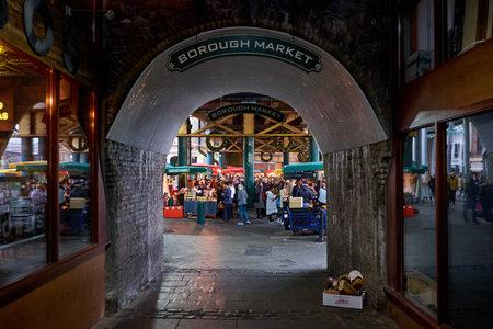 LONDON CITY - DECEMBER 24, 2016: Entrance with hanging signs to Borough Market under the railway tracks near London Bridge