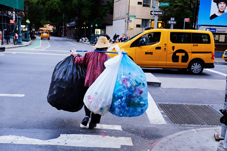Person collecting a lot of bottles and cans in the streets of Manhattan Editorial