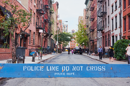 NEW YORK CITY - OCTOBER 10, 2014: Standing behind a police barrier looking down Leroy Street, with people walking by