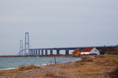 Great belt bridge seen from the Sealand side with two small houses on the coastline Stock Photo