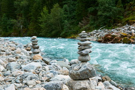 Small rocks stacked by the gushing river floating from Folgefonna glacier through Buerdalen in Norway Stock Photo