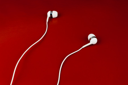 White earphones on a red leather surface