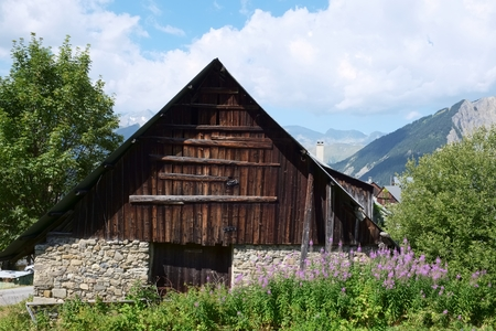 Old ramshackle barn made of boulders and wood, situated in Albiez Montrond in the french alps. Mountain tops is seen in the back