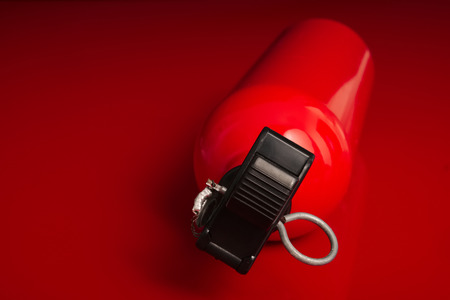 A small fire extinguisher lying on a red surface with the top nozzle pointing out of the image Stock Photo