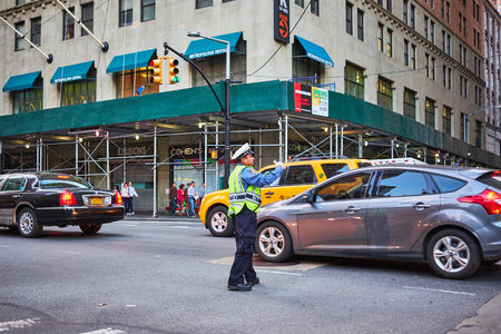 NEW YORK CITY - OCTOBER 10, 2014: A NYPD trafic officer conducting the traffic on Broadway in the Tribeca area
