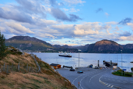 LAUVVIK, NORWAY - OCTOBER 11, 2015: The small ferry berth and quai in Lauvvik, the ferry on the water is on its way to Oanes