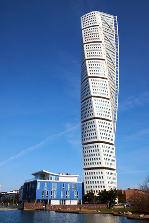 MALMO, SWEDEN - MARTS 28, 2014: Turning Torso tower building standing next to a small apartment building in West Harbour