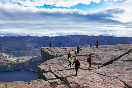 PULPIT ROCK, NORWAY - OCTOBER 12, 2015: People walking, hiking and standing on the Pulpit Rock outcrop, 600 meters above the Lysefjord