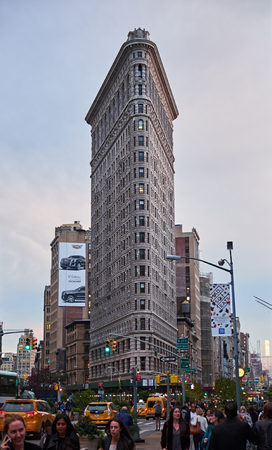 NEW YORK CITY - OCTOBER 10, 2014: stree level view to the Flatiron building, with people and traffic in the foreground Editorial