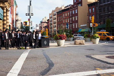 NEW YORK CITY - OCTOBER 16, 2014: Large group of orthodox hasidim jews waiting for green light, on the corner of Bedford Avenue and Broadway in Williamsburg