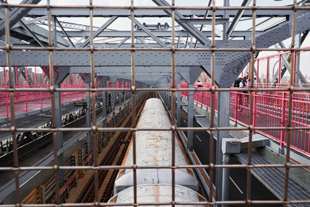 NEW YORK CITY - OCTOBER 16, 2014: overlooking the rail tracks and a trains roof on Williamsburg bridge, through a steel grid
