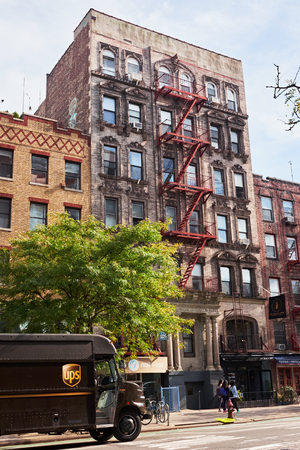 NEW YORK CITY - OCTOBER 16, 2014: Typical old Lower Eastside apartment (tenament) building with an attached steel fire escape stair on the facade facing the street, on 2nd Avenue Editorial