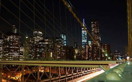 NEW YORK CITY - OCTOBER 18, 2014: Financial district skyline illuminated at night, seen from a night walk on Brooklyn Bridge