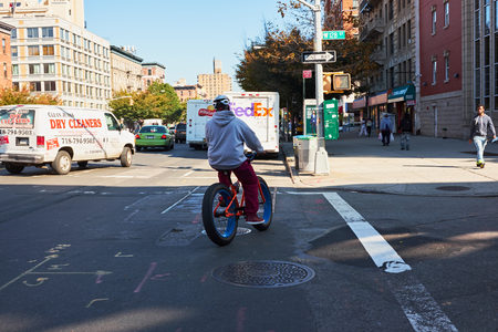 NEW YORK CITY - OCTOBER 17, 2014: young man riding his cool bike with fat tires on Lenox Avenue in Harlem