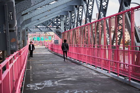 NEW YORK CITY - OCTOBER 16, 2014: an orthodox jew and a man in leather jacket walking the Williamsburg Bridge on Brooklyn side