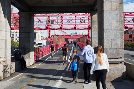 NEW YORK CITY - OCTOBER 16, 2014: people walking, riding and jogging at the entrance of the Williamsburg Bridge on the Manhattan side