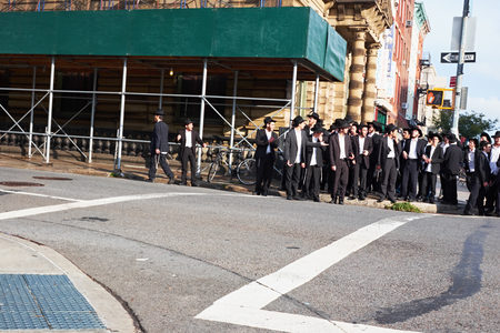 NEW YORK CITY - OCTOBER 16, 2014: big group of happy orthodox jewish men, ready to cross the street on Bedford Avenue in Williamsburg