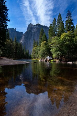 Rock and trees reflecting in a river in Yosemite National Park