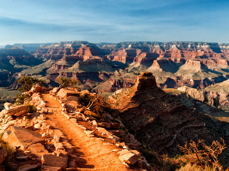 View Point in the Grand Canyon in the forground with a long path leading down into the canyon