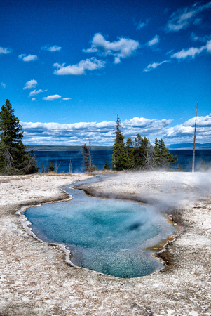 Blue hot spring in Yellowstone National Park, close to the Yellowstone Lake in the background