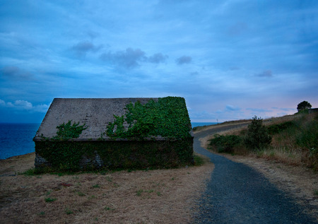 Deserted barn at the coast of Normandy at sunset, France