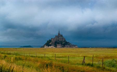 Mont Saint-Michel behind a yellow, green field Stockfoto