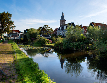 Early in the morning the church and houses reflected in the abundant water in and around the village of Marken Stockfoto