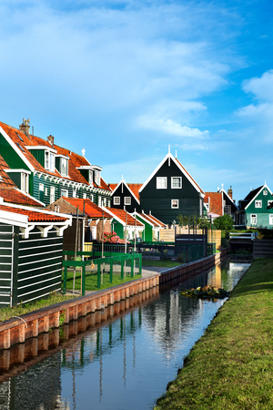 The houses with the typical orange roof tiles reflected in one of the many canals of Marken, an old town at the IJsselmeer in the Netherlands.