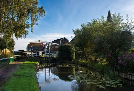 The white drawbridge, called Maxima Bridge named after the Dutch princess and wife of our King in Marken is nicely reflected in the water of the canal.
