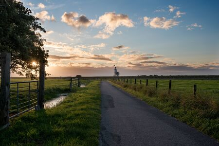Road leading us to the famous lighthouse of Marken, called Horse of Marken, translated as Horse of Marken, in a nice light during sunrise. Stockfoto