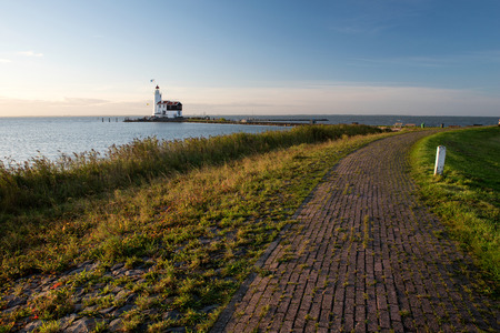 The idyllic lighthouse of Marken at sunrise, seen from the dike protecting the village of Marken from the water