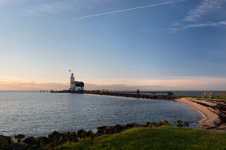 Panorama of the or Lighthouse of Marken, called Horse of Marken, translated as Horse of Marken in the morning sun on the shore of the IJsselmeer in the North of Holland.