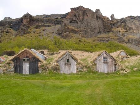 Een rij van traditionele IJslandse huizen met de daken bedekt met graszoden voor isolatie.