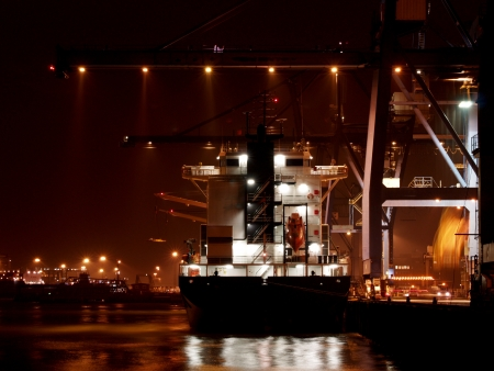 A ship at the docks being loaded with containers at night. photo