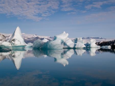 Ijsbergen in IJsland drijvend op een mooie blauwe zee. Stockfoto