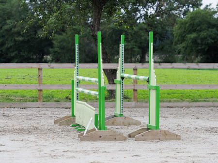 A single show jump fence in a typical riding arena. Imagens