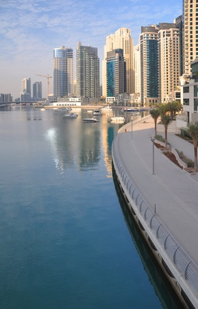 The sun rises on the superb Dubai Marina surrounded by luxury high rise apartments  Stock Photo
