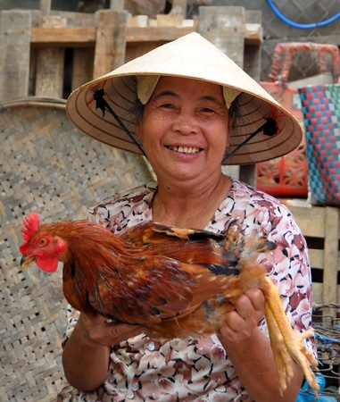 An elderly woman vendor offers a live chicken for sale in the markets of Hoi An in central Vietnam. Editorial