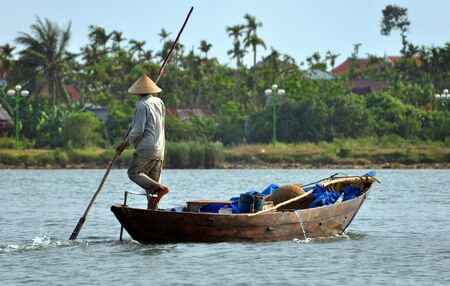 hoi an: A fisherman paddles his boat home on the Hoi An river. Note how he steers with his foot. Hoi An, Vietnam - April 16 2009. Editorial
