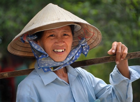 Ho Chi Minh City, Vietnam - April 15, 2009: A woman in a traditional Vietnamese hat takes a break from selling fruit and vegetables.