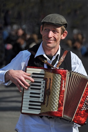 busker: Spring in Greenwich Village, New York. A Busker plays a red Weltmeist Piano Accordion in the streets of Greenwich Village, New York on April 09, 2008. Editorial