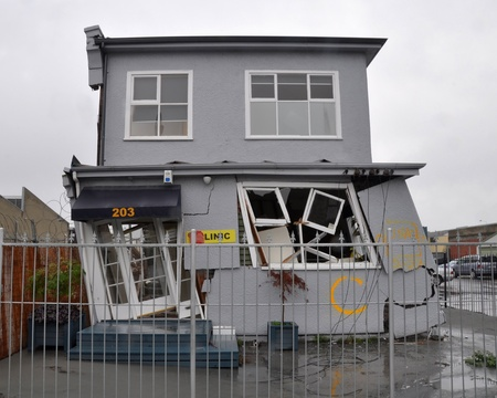 leans: Christchurch, New Zealand - March 20, 2011: A house in the east of the city leans precariously after the 22 Februray 2011 earthquake. A red sticker next to the front door indicates it is too dangerous to enter on March 20, 2011 in Christchurch. Editorial