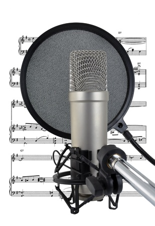 Professional level condenser vocal microphone, pop-shield and sheet music for studio recording a singer  Isolated on white background