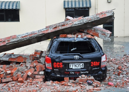 Christchurch, New Zealand - March 2011: A car is crushed by a collapsed brick wall on March 20, 2011 in Christchurch following a 6.2 magnitude earthquake.