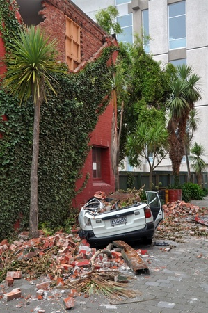 Christchurch, New Zealand - March 2011: A car is crushed by a collapsed brick wall on March 12, 2011 in Christchurch following a 6.2 magnitude earthquake.