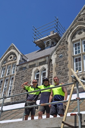 Christchurch, New Zealand - January 2011: A team of three happy builders are re-tiling the damaged roofs of Julius and Harper Houses at Christs College on January 14, 2011 after severe earthquakes in Christchurch.