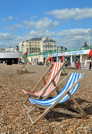 Brighton, United Kingdom - April 16, 2012: Red & Blue striped Deck Chairs await the tourists on the beach during a Spring day at Brighton.
