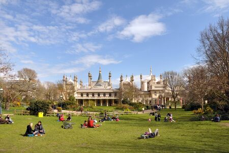 Brighton, United Kingdom - April 16, 2012: Tourists on the grass enjoying a Spring day infront of historic Brighton Pavillion.